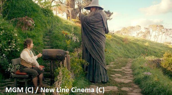 """Gandalf rozmawiający z Bilbem na ganku.  """"Hobbit: Niezwykła podróż"""" – plan filmowy Hobbiton w Nowej Zelandii."""